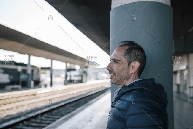 Attractive man waiting for a train at a station