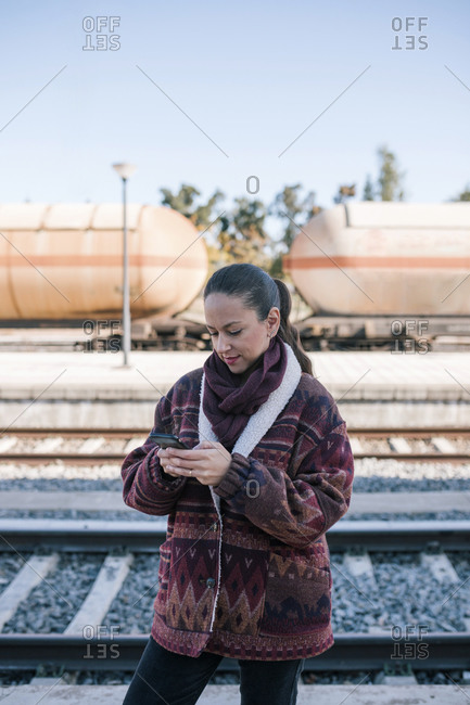 Young woman looking at her mobile phone in a train station in Spain