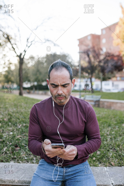 Portrait of 40-year-old man listening to music with headphones outdoors