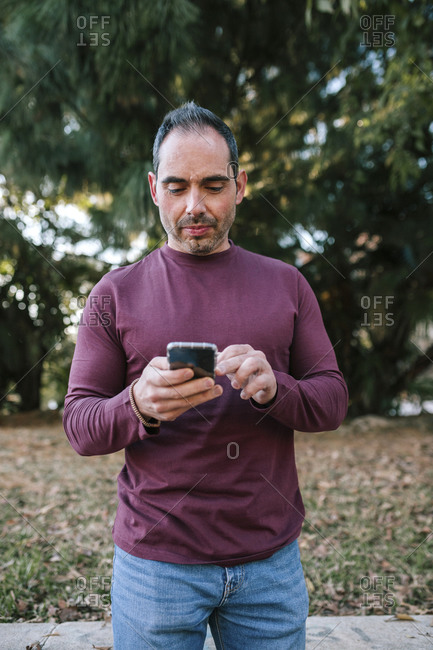 Young man of 40 years looking at his mobile phone in a park
