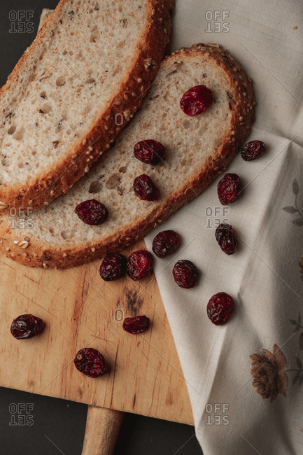 High angle view of two slices of integral bread with a lot of dried red cranberries over a wooden cutting board and a napkin.