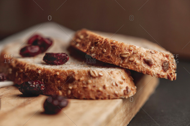 Close up detail of two slices of integral bread with some red cranberries over a wooden cutting board and a napkin, dark moody food.