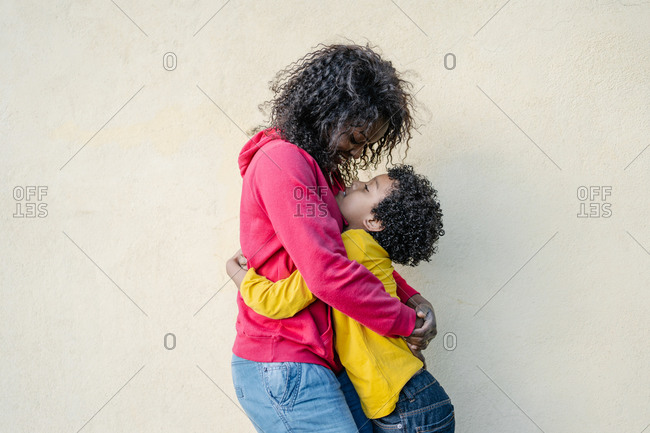 Mother and son dressed in colorful casual clothes hugging each other tenderly outside with a yellow wall in the background