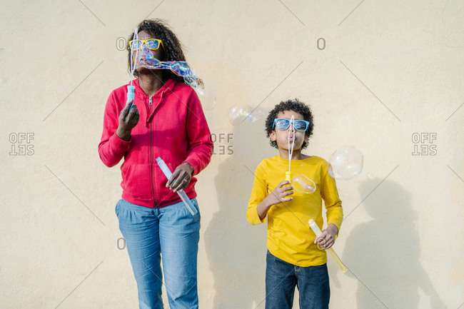 African-American mother and son dressed in colorful casual clothes playing and making soap bubbles outside