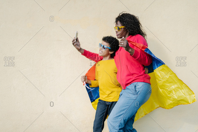mother and son dressed in colorful casual clothes and sunglasses covering themselves with the Colombian flag while making a selfie