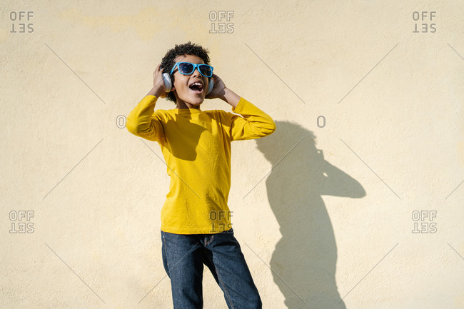 A happy black boy with curly hair listening to music on her headphones on yellow wall on background