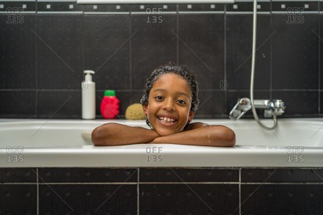 Happy black kid sitting in a foam bath leaning on the side