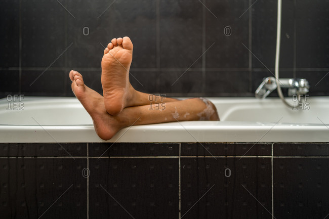 Front view of a black child's feet on edge of bathtub