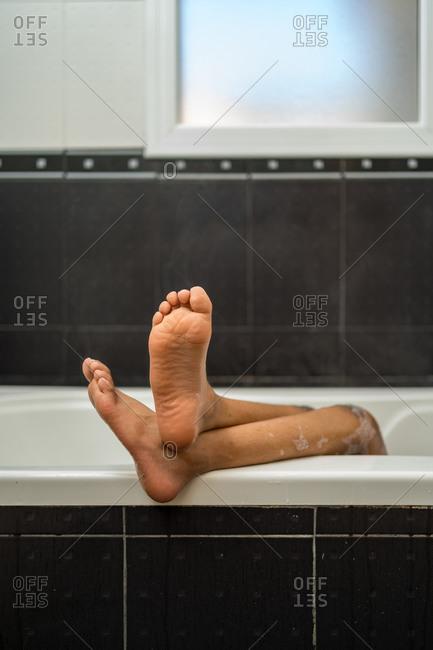 Black boy's feet sticking up on edge of bathtub. Vertical shoot