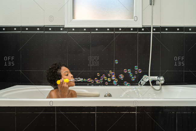 A black child playing with soap bubbles in a bubble bath