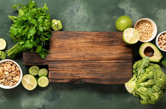 Vegan menu concept. Fresh green vegetables and grain with old wooden kitchen board top view