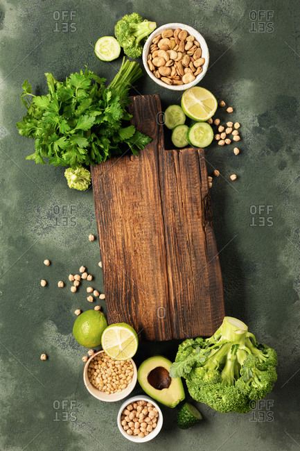 Vegetarian menu concept. Fresh green vegetables and grain with old wooden kitchen board top view
