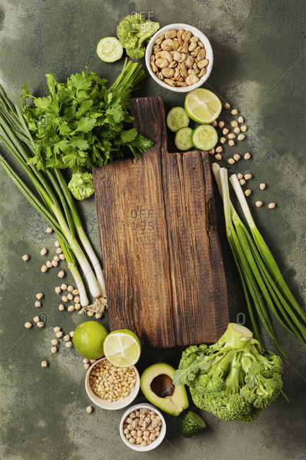 Vegetarian menu concept. Old wooden kitchen board with fresh green vegetables and grain top view