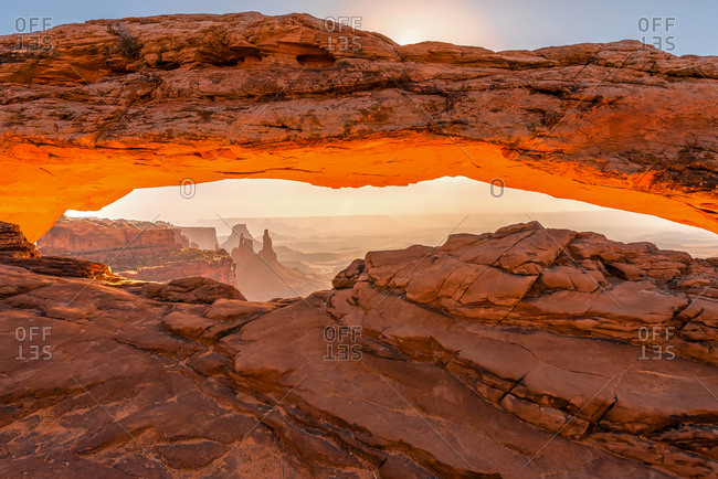 Early morning view of famous Mesa Arch with sunrise light reflecting from below in Canyonlands National Park