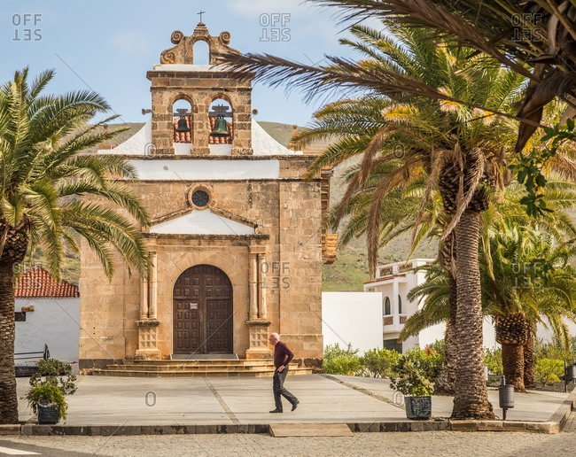 VEGA DE RIO PALMAS, SPAIN - FEBRUARY 2018: Man walking in from of the church of Nuestra Senora de la Pena in Fuerteventura.