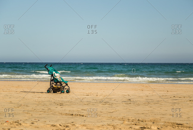Beautiful empty sandy beach with an infant baby stroller in Fuerteventura, Canary Islands, Spain.