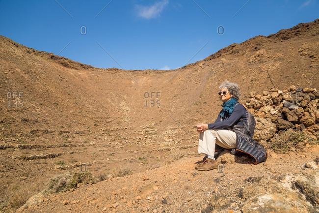 Woman sitting in Caldera de Gairia volcano cone in Fuerteventura, Canary Islands, Spain.