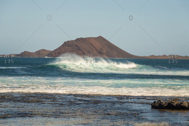 Large waves blown in the wind in front of Isla los Lobos near Corralejo, Fuerteventura, Canary Islands, Spain.