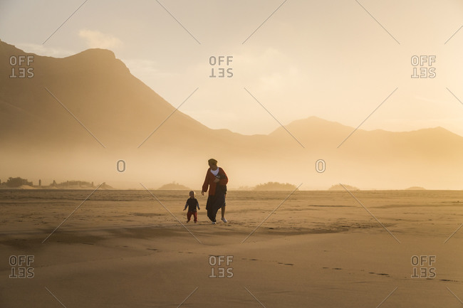 Silhouette of a young mother with her little child walking on sunshine in Cofete, Fuerteventura, Canary Islands, Spain.