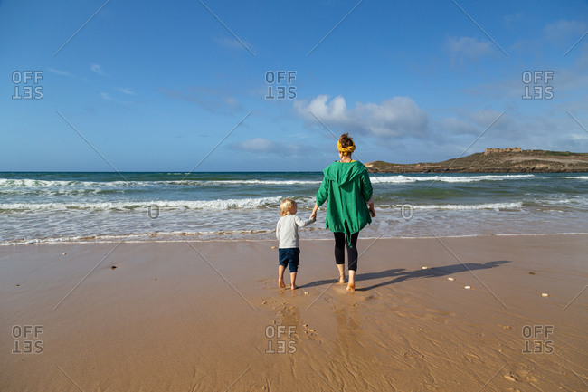 Mother and son standing on sandy beach in Portugal.