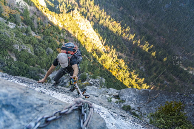 Man with hat looking down jugging rope up with backpack on El Capitan