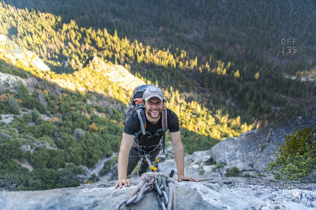 Man smiling while looking up jugging rope on East Ledges El Capitan