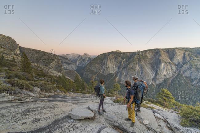 Three hikers looking at Half Dome from El Capitan sunset Yosemite