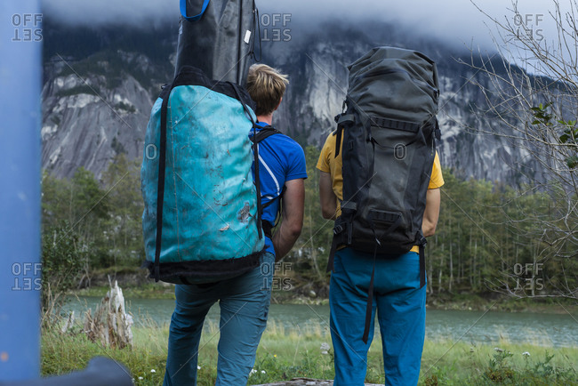 Two people with big backpack standing in front of mountain and river