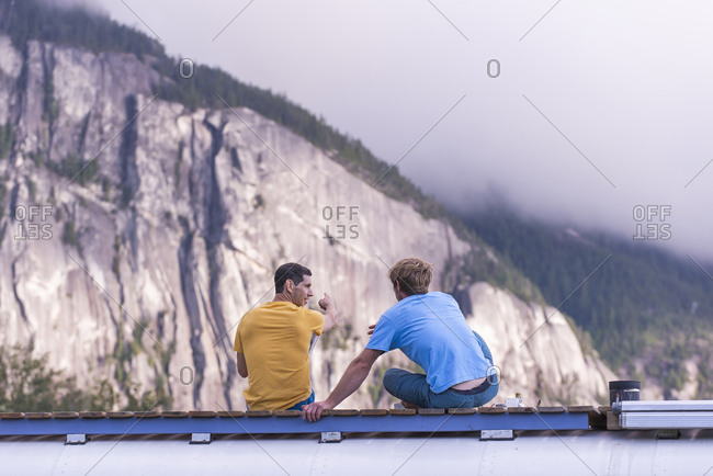 Man pointing out rock climbing cliff with finger on top of school bus
