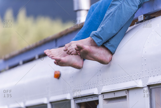 side view of bare feet hanging from roof of school bus two people