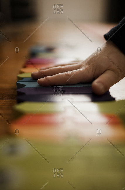 Preschooler boy's hand putting together a brightly colored puzzle