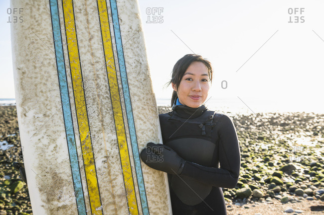 Smiling Asian Woman with a healthy lifestyle going winter surfing