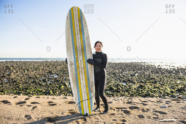 Long Shot portrait of healthy Asian Woman going winter surfing