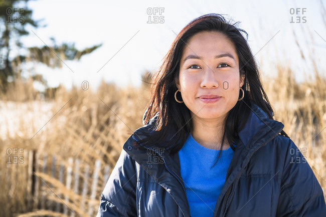 Closeup Portrait of Asian Woman outdoors smiling at the beach