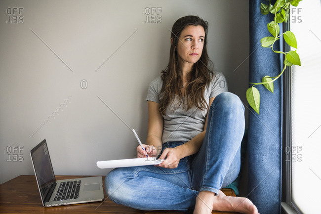 Lonely individual woman on her laptop working / studying at home