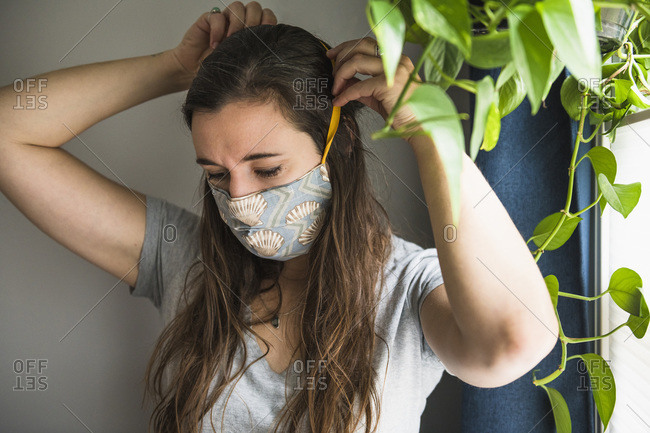 Woman indoors at home with homemade face mask protection PPE