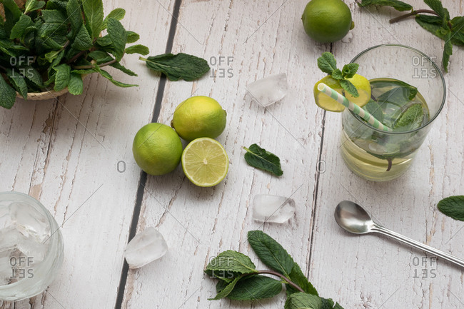 Top view of a mojito cocktail and its ingredients on a white rustic table
