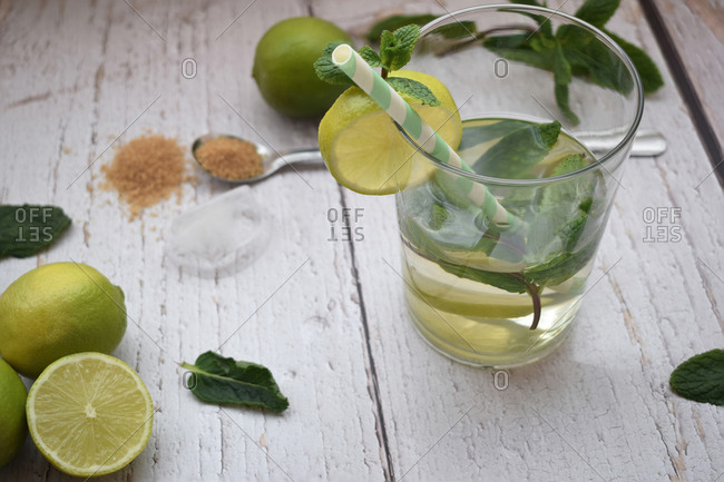 Glass of mojito with mint, lime and brown sugar on a white table