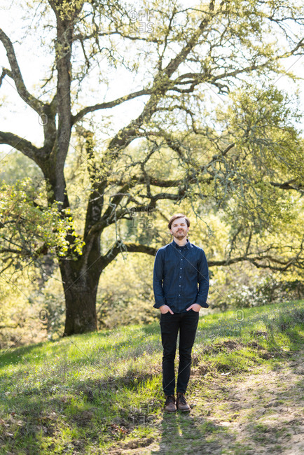 Full body portrait of man in casual clothes in front of Oak tree