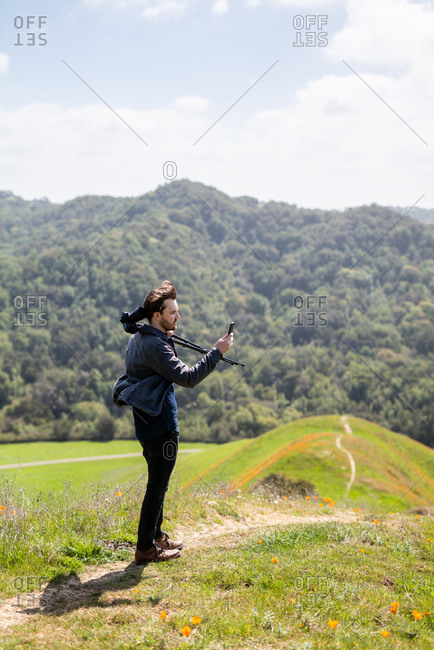 Young man takes photo with phone while holding camera over shoulder