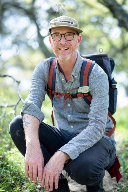 Portrait of backpacker kneeling on trail and smiling in California