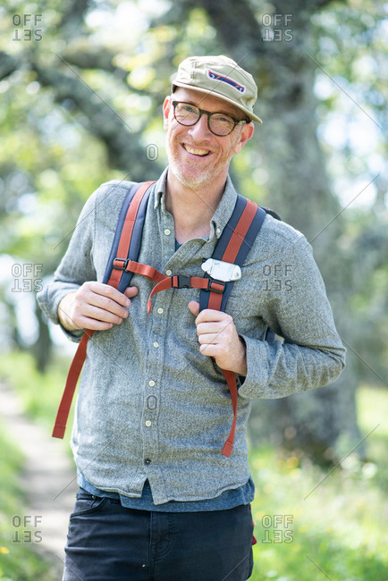 Portrait of smiling hiker with hat, glasses, and backpack outdoors