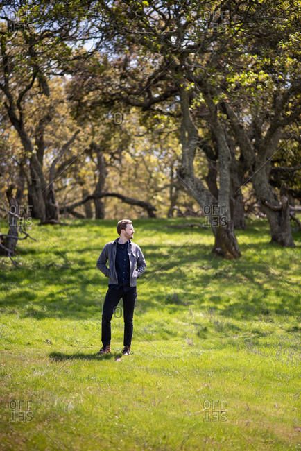 Full body portrait of young man casually dressed outdoors with trees