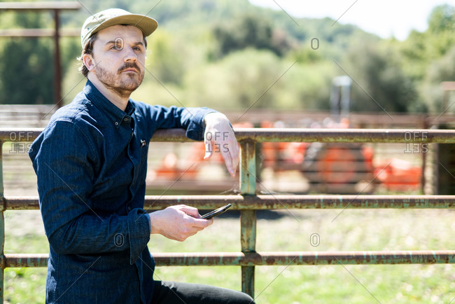 Young Farmer looking into distance holding smart phone leaning on gate