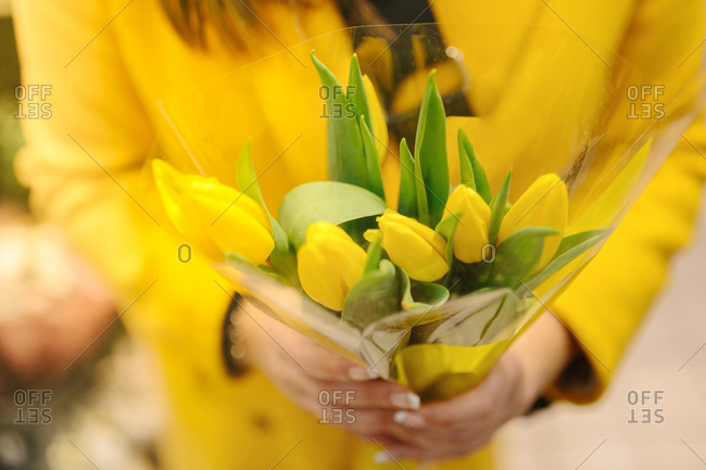 Unrecognizable woman with a bouquet of yellow tulips. She just receive