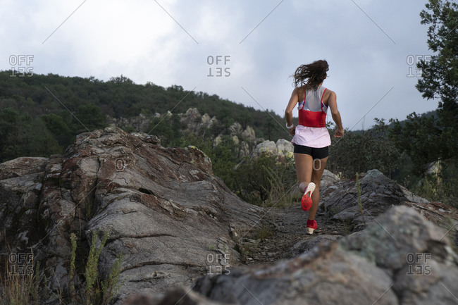 One woman seen from behind running on a trail