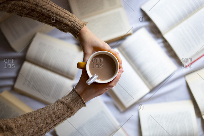 Hand picking up a cup of warm coffee with books.
