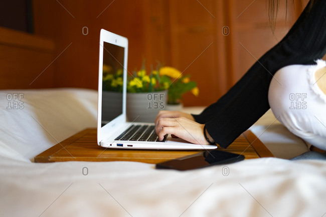 Woman working in bed with the computer.