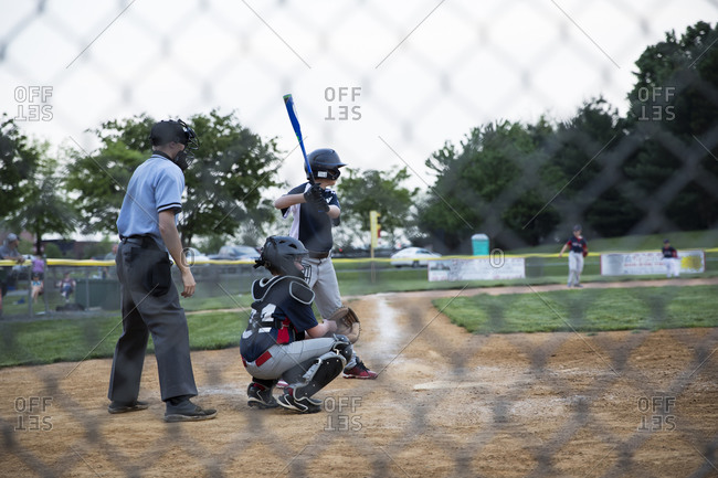 Wide rear view of teen boy at bat during baseball game