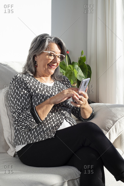 Smiling old lady sitting on a sofa and using a smartphone mobile